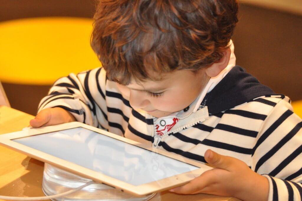 タブレットを覗き込む子どもの写真